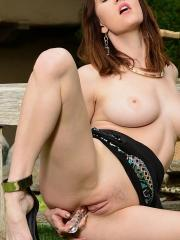 Amber Hahn lifts her dress to toy her pussy with a glass dildo