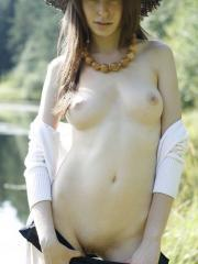 Brunette model Lena displays her nude body outside in a hat