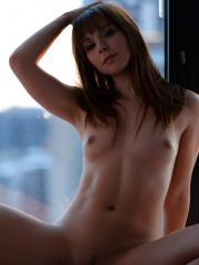 Ariel Rebel strips next to the window at sunset