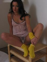 Brunette teen pulls off her socks to show her pretty soles