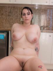 Brunette girl Chloe Jenks shows you her huge tits in the kitchen