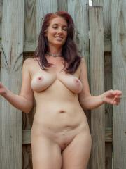 Busty redhead Andy Adams gets naked outside