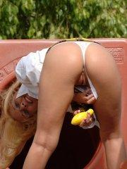 Pictures of a blonde schoolgirl toying her pussy in a park