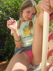 Cute teenage babe Shelby takes a smoke break and flashes us her perky tits