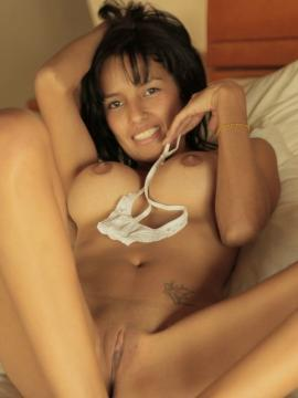 Celeste lays in bed as she softly removes her lace underwear