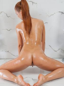 Stunning redhead Carinela gets all slippery and shiny for you