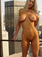 Blonde babe Naughty Allie shows off her huge boobs by the window