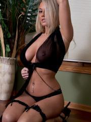 Busty blonde Nikki Sims poses in her black lingerie