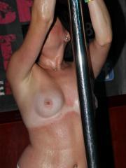 Hot coeds participate in a wet t-shirt competition with stripper poles
