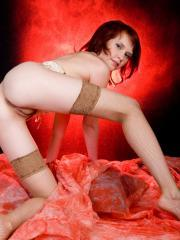 Redhead girl Anelie A shows off her tight body in fishnets