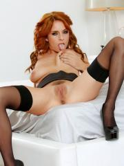 Redhead babe Ashlee Graham plays with her pussy in bed